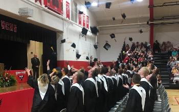 The Class of 2019 throw their caps toward the sky.