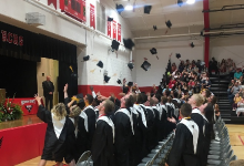 The Class of 2019 throws their caps toward the sky.