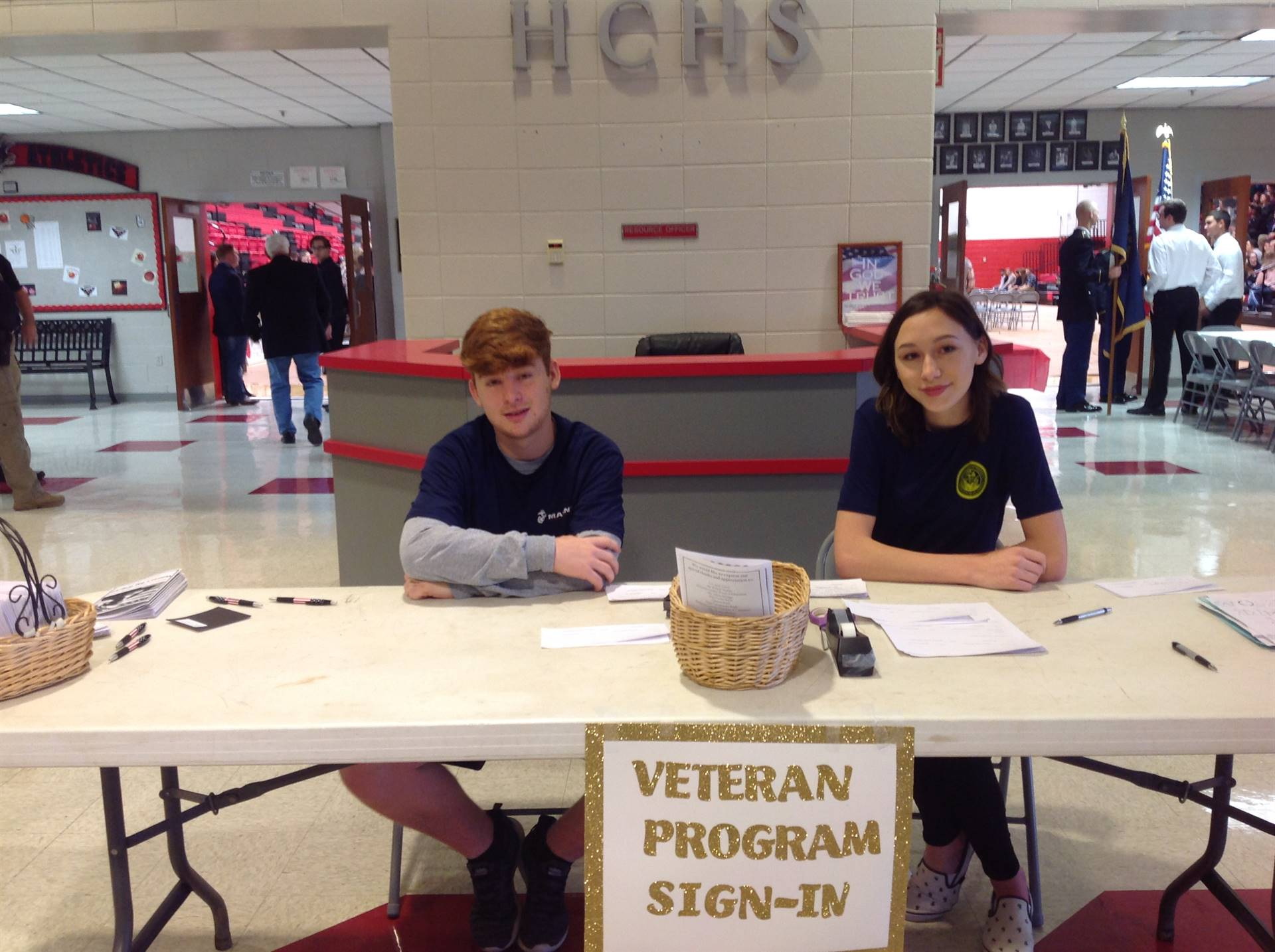 Two members of the Military Club greet veterans and their families.