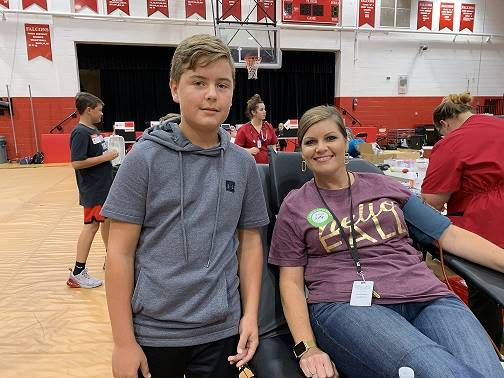 A student poses with his mom who donated blood.